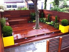 A red-stained deck is surrounded by a privacy fence and low-maintenance landscaping. Yellow planters and simple built-in benches are contemporary additions to the outdoor space. Contemporary Living, Contemporary Planters, Deck Design, Garden Design, Outdoor Spaces, Outdoor Living, Outdoor Ideas, Garden Sitting Areas, Gardening