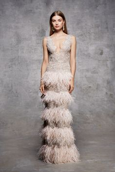 Plunging V neckline fully beaded sleeveless silver metallic lace column gown with encrusted honeycomb beading, metallic threadwork flowers and tiers of ostrich feather fringing.