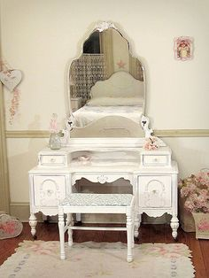 This gorgeous vanity is an old time beauty with all its fancy scallops and curves. The vanity and bench are refinished a linen white and lightly distressed. There are two small drawers on top and two lower drawers with newly added glass knobs.