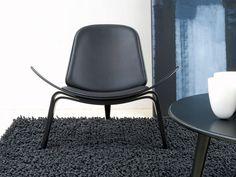 The Carl Hansen CH07 Shell chair in Black Beech is a sculptural easy chair with a triangular footprint.