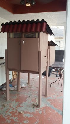 Chicken Coop made from two kitchen cabinets.  One single and one double...take backs off both cabinets...turn the single cabinet sideways and attach to double cabinet for  cabinet. nesting area...add legs and roof...cut door in side and add a ladder.