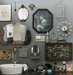 collage of curiosities on bathroom wall: mirrors, vintage photos, butterfly specimens