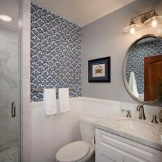 Cresting waves make a compelling graphic backdrop in this petite bathroom. Keeping the wallpaper only in select areas of the room keeps the pattern from overwhelming the space.
