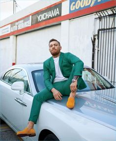 Sitting on a Rolls-Royce Wraith, Conor McGregor wears a custom green suit by David August Couture. McGregor also dons a Velva Sheen sweatshirt with Christian Louboutin loafers.