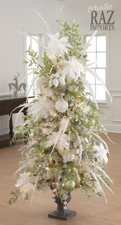 RAZ 2011 Christmas Trees - perfect tree for small spaces. Potted Tree with lots of white poinsettias and feathers. Shop Trendy Tree for RAZ Christmas decorations! Flocked Christmas Trees, Beautiful Christmas Trees, Elegant Christmas, Noel Christmas, Winter Christmas, Christmas Wreaths, Christmas Topiary, Xmas Trees, Primitive Christmas