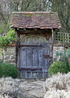 An overhang of tiles and a rustic wood door blend perfectly with field stone and faded lavender, making this garden scene one of artistic perfection. Photo by Lars Plougmann.