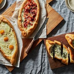 3 types of Khachapuri. From left to right: egg and cheese, crispy prosciutto-rosemary, and green khachapuri.