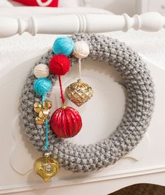 Be Merry Knit Wreath Free Knitting Pattern from Red Heart Yarns - Knitting this wreath is just like knitting a simple scarf! Bulky yarn looks great and works up quickly, then you can use decorations to fit your personal holiday style and color scheme.