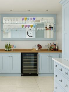 Mirror-backed open wall cupboards with glass shelves create a glamorous focal point within the kitchen. Beneath it, a wine fridge is flanked by twin drinks cupboards. Martin Moore Kitchens, Sky Blue Paint, New Classic Furniture, Wall Cupboards, Chimney Breast, Long Walls, English Kitchens, Open Wall, Handmade Kitchens