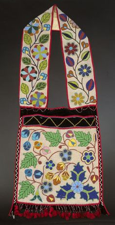 "Chippewa Beaded Bandolier Bag, is beaded in blues, greens, reds, and yellows against pearl opalescence on black velveteen. Bag has an elaborate floral pattern with white and yellow zigzag border, mauve beaded loops under straps, matching beaded fringe with red cotton yarn tassels at bottom, 45.5 x 18""."
