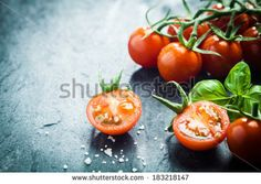 Fresh grape tomatoes with basil and coarse salt for use as cooking ingredients with a halved tomato in the foreground with copyspace by stoc...