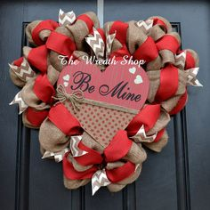 This sweet Valentines Wreath is done on a heart shaped frame with burlap as the base, and solid red and ivory chevron ribbons accenting it. A