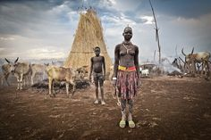 A young woman in traditional clothes in front of her thatched hut in a Mundari cattle camp.