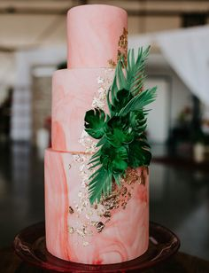coral pink marble cake with gold leaf and tropical leaf accent
