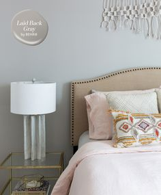 Modern Romantic Bedroom | Grey walls add sophistication to an eclectic space. Here, designer Carmen Collins chose BEHR®️ Laid Back Gray T17-09 to balance a nailhead-trimmed headboard and blush linens. | Photographer: Molly Winters Culver | #sponsored #behr #behrpaint #paintcolour #paintcolor