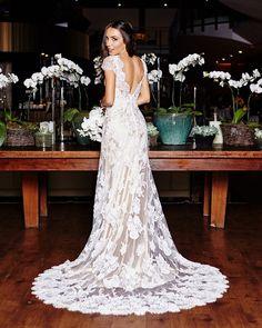 Vestido de noiva rendado, com um decote nas costas e manga curta.