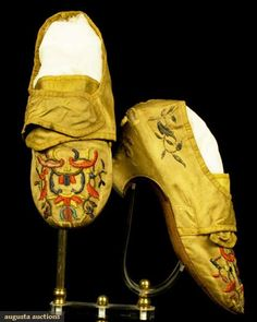 """LADY'S EMBROIDERED SILK SHOES, 1750-1760. Dull gold satin, originally golden yellow (seen under tongue), blunt round toes, low squat heels, crossover latchets for shoe buckle fastening, vamps embroidered in multicolor silk floss, heels & shoe back embroidered w/ metallic silver flowers, white kid latchet & back heel lining, vamps lined in homespun linen, (very soiled, minor wear to toe boxes, above back heel one .25""""x1"""" hole on each shoe) fair. BM"""