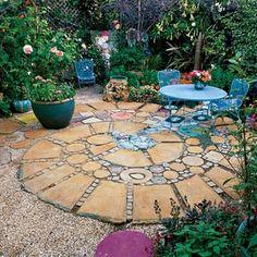 mosaik im garten stilisierte Schnecke aus Steinen