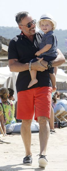 Adorable dudes! David looked stylish in a black T-shirt and red boardshorts as he carried ...