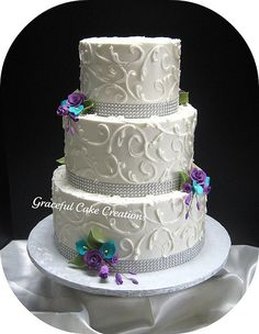 Elegant+White+Wedding+Cake+with+Crystal+Ribbon+accented+with+Teal+and+Purple+Flowers