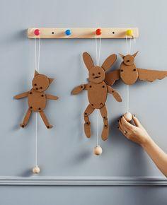 GIF animado de tres muñecos hechos con cartón colgados de un perchero en la pared.