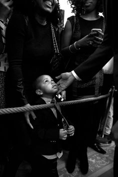 A young child dressed in a suit looks up at the unseen face of the president, as Obama reaches down and his mother stands behind him