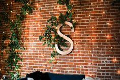 Mid Century Modern styled wedding decor with a custom copper monogram wall decor, lights, and greenery. Photo by Brian Flint, Floral by DeClerk Wray Designs, Wedding Planning by Bella Baxter Events.