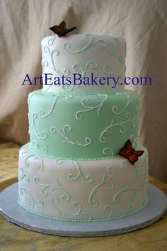 Three tier mint green and white custom unique wedding cake design with curlicues and edible butterflies by arteatsbakery.