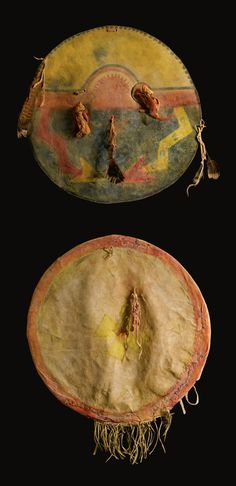 COMANCHE PAINTED HIDE SHIELD & COVER composed of buffalo hide, painted in red, yellow & blue pigments, with a buffalo face flanked by radiating zigzag bands, perhaps a reference to lightning, surmounted by concentric bands, tied with a pair of circular hide pendants & pouches, & three turkey feather attachments (replaced); together with a finely tanned, fringed elk hide cover, of drawstring construction, painted in red & yellow, with a Spanish-style cross enclosed by a series of triangles.