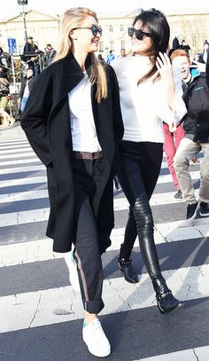 Left, Gigi Hadid wears a white top, embroidered jeans, platform sneakers, and a black jacket. Right, Kendall Jenner wears a a white sweater, leather pants, and Saint Laurent ankle boots