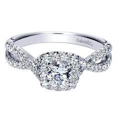 14K White Gold .67cttw Criss-Cross Halo Diamond Engagement Ring. This ready to wear diamond engagement ring, features 2/3cttw of round diamonds with a criss-cross shank and cushion shaped halo. The ce