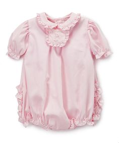 Trimmed with charming ruffles and boasting a soft hue, this lovable selection lends a homespun touch to your little one's look.
