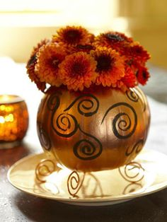 Gilded Gourd: A painted sugar pumpkin filled with mums makes a pretty autumnal centerpiece. Get the easy how-tos.  #autumn #fall