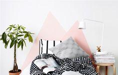 Das Bild zeigt ein Bett mit Kissen, dahinter eine gestrichene Wand.