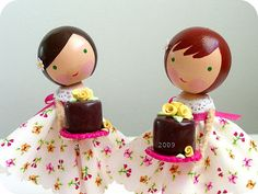 Clothespin dolls in matching dresses each holding chocolate cakes.