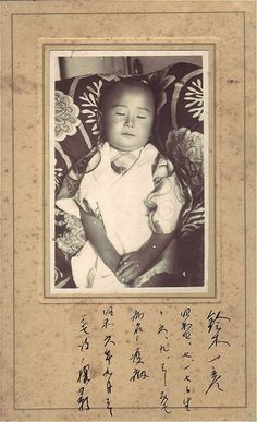 A rare memento mori post-mortem photograph from the Orient. Young boy, propped on pillows. Wish I knew what country this was from (vertical writing makes me think Japan or China), and what the words below the image said. Is it a prayer? A dedication?