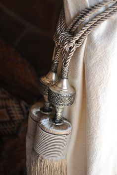 Handmade Moroccan (cactus) silk curtain ties in taupe. A white brass ornament with intricate design, fine silk tassels and thick robe ties that can easily be tied around a curtain. They also look gorgeous as hanging decoration at the ends of a curtain pole, on a mirror, a headboard, wardrobe knob etc.