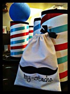 made mystache candy bags, tied with black bow... barber shop lamps with white balloons on them instead of blue, but the one shown was my practice. Covered paper towel rolls in white thin sticker like paper, glued ribbons around according to theme colors. Placed them on top of black charger plates also shown on board. The mustaches on goodie bags are also made with felt