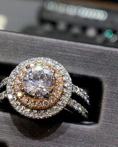 We love this double halo engagement ring with rose gold accents and round diamond center stone!