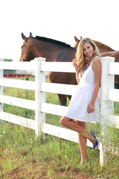 Little white dress with pops of cobalt blue in a field of of horses