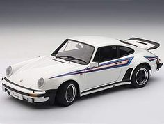This Porsche 911 Turbo 3.0 (Martini Stripes 1976) Diecast Model Car is White and features working steering, suspension, wheels and also opening bonnet, boot with engine, doors. It is made by AUTOart and is 1:18 scale (approx. 23cm / 9.1in long).  ...
