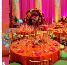 Centerpieces -- A mixture of round and rectangular tables featured tightly-packed spheres of saffron, burgundy and fuchsia blooms. The fragrant globes sat atop regal candelabras with beads draping down for extra glamour. Centerpieces: A Vista Events, Beltsville, MD -- Photo By: RodneyBailey.com, Fairfax County, VA