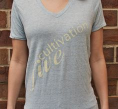 Girls V-Neck Eco Oatmeal - Cultivation Five is a T-shirt line that joins style, comfort and class with giving back to the community.  Partnering with children's charities, the company donates $5 to the charity chosen by you, the consumer, with each T-shirt sold.  With your purchase, you will also be provided with a handmade drawstring bag.  #C5 #CharityFashion #GiveBack