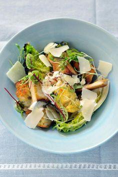 Bereiden:Verwijder de buitenste bladeren van de slaharten en snijd overlangs door.Snijd de ciabatta in blokjes van 1 cm bij 1 cm. Verhit een scheut olijfolie in de pan en voeg het geplet knoflookteentje toe. Rooster de broodcroutons goudbruin en laat uitlekken op keukenpapier.Maak de dressing. Mix de eierdooiers, mosterd, citroensap, hazelnoten, geraspte parmezaankaas, worcestersaus, look en zure room.Klop er geleidelijk aan de olijfolie onder tot een dik vloeibare dressing. Breng op smaak…