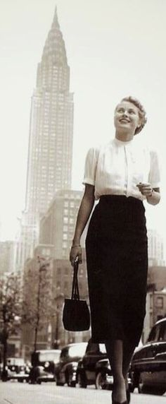 Grace Kelly taking on the BIG APPLE... New York in 1956...wearing a pencil skirt, short sleeve button down shirt & carrying a tiny clutch bag (trending again now.)