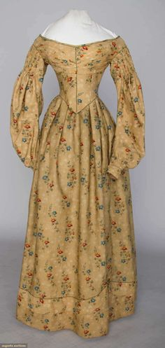 """PRINTED WOOL DAY DRESS, c. 1838  Brown light weight wool ground, blue & red floral print, green bodice piping, sleeve tops gathered, B 30"""", W 22"""", L 53"""", (small period mends throughout)"""