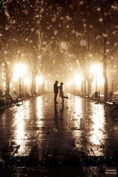 Lights and rain, couple romantic embrace
