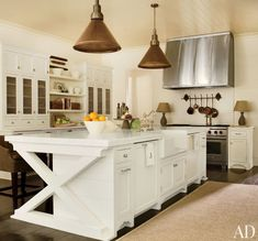 Notice the contrasting brass fixtures & the beautiful detailing on the island in this kitchen by Suzanne Kasler.