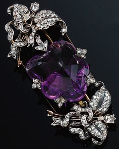 AMETHYST AND DIAMOND BROOCH/PENDANT, LATE 19TH CENTURY. The pentagonal facetted amethyst encased within diamond-set claws, to two lateral motifs embellished with foliate ribbons, set throughout with rose-cut diamonds, collapsible pendant fitting, detachable brooch fitting.