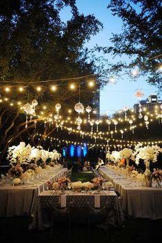 Resalta tus centros de mesa con la iluminación de la boda. Esta decoración con luces para bodas es sencilla de hacer. Solo precisas tiras de lamparitas expuestas y unos caireles colgantes que reflejen su luz. El cristal de las mesas aumentará mas su brillo.